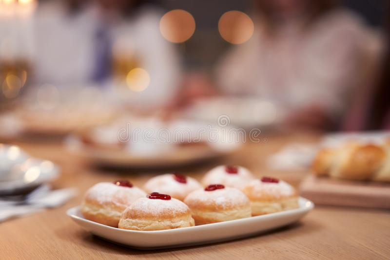 Hanukkah dinner. Family gathered around the table with traditional dishes royalty free stock photo