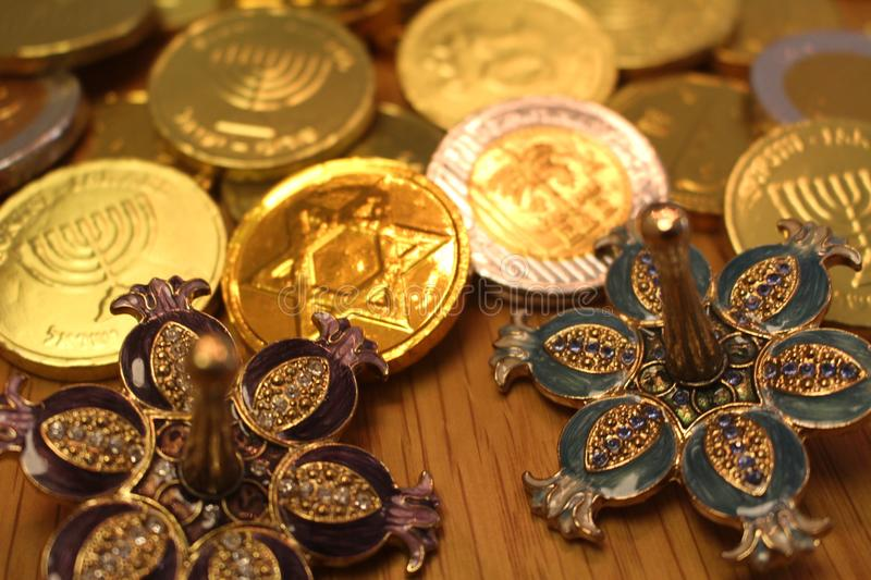 Hanukkah gelt chocolate coins with star of David on back and silver dreidel with pomegranate stock photos