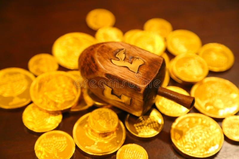 Hanukkah gelt złociste monety i dreidel na stole obraz royalty free