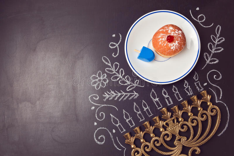 Hanukkah holiday background with menorah and sufganiyot over chalkboard. View from above royalty free stock photos