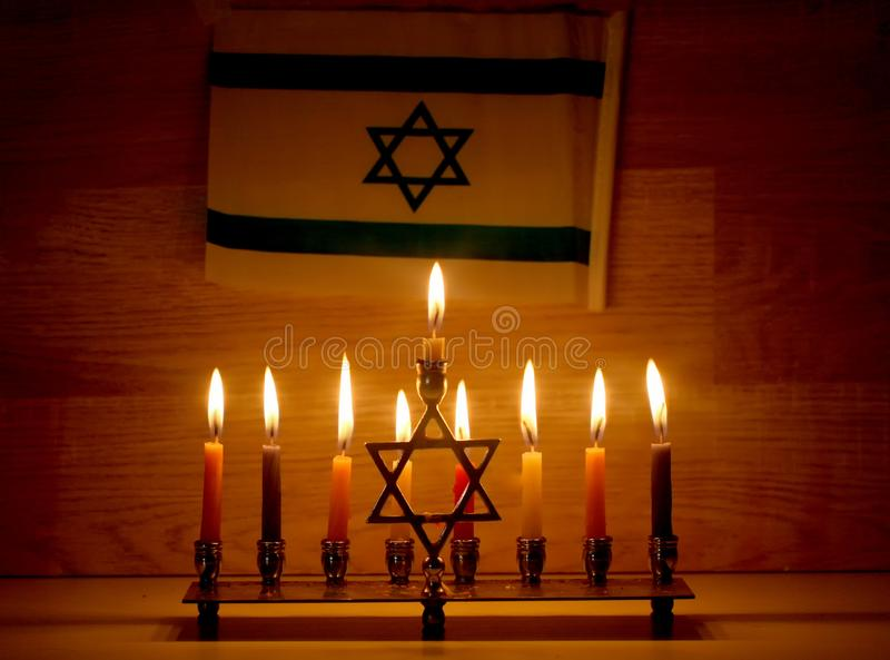 Hanukkah is a Jewish holiday. Burning Chanukah candlestick with candles. Chanukiah Menorah. Flag of Israel royalty free stock images
