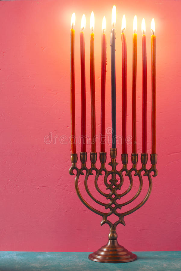 Hanukkah menorah with burning candles on the pink background vertical royalty free stock image