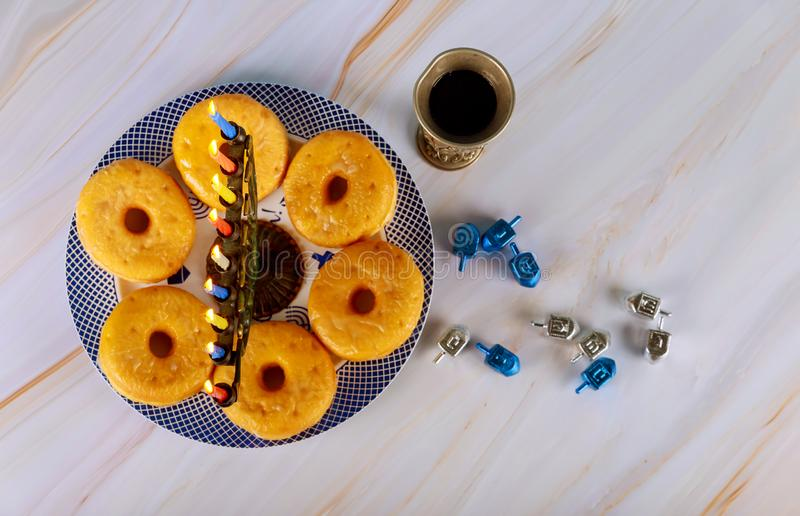 Hanukkah menorah and donuts on plate with wine and dreidel royalty free stock photo