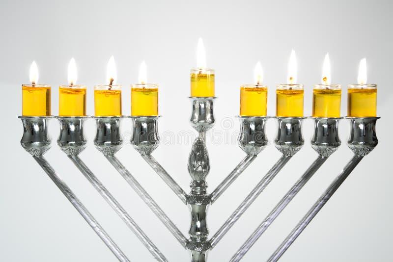 Hanukkah Menorah / Hanukkah Candles. Silver Hanukkah candles with oil candles, all candles lite on the traditional Hanukkah menorah stock image