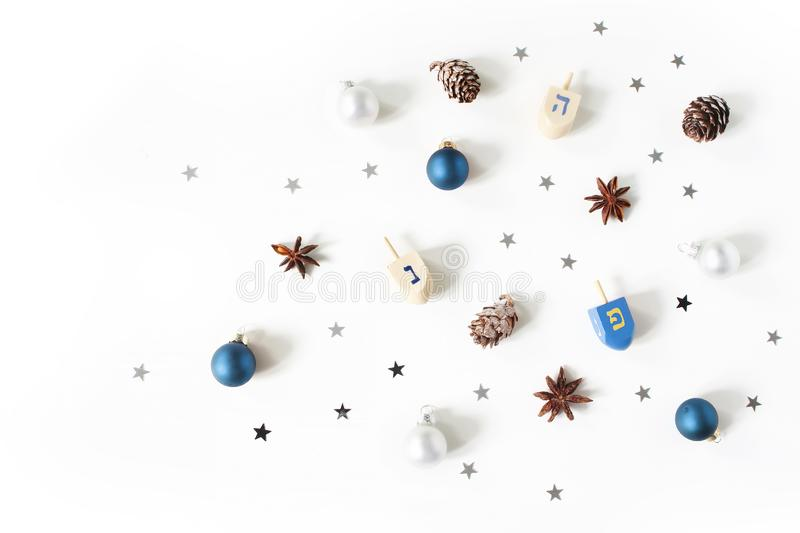 Hanukkah styled stock composition. Decorative pattern. Wooden dreidel toys, larch cones, anise and silver confetti stars royalty free stock images