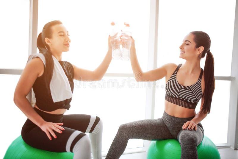 Haooy młode kobiety cheerfing wpólnie Siedzą na zielonych fitballs i dotykają each - inny butelki Modele patrzeją szczęśliwymi obrazy royalty free