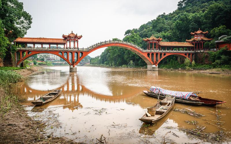 Haoshang arch bridge in oriental Buddha park and small fishing boats on the river in Leshan China. Haoshang arch bridge in oriental Buddha park and small fishing royalty free stock images