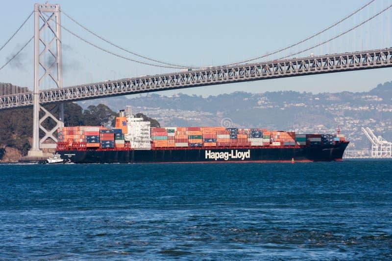 Hapag劳埃德移动在奥克兰海湾桥梁下的集装箱船 免版税库存照片