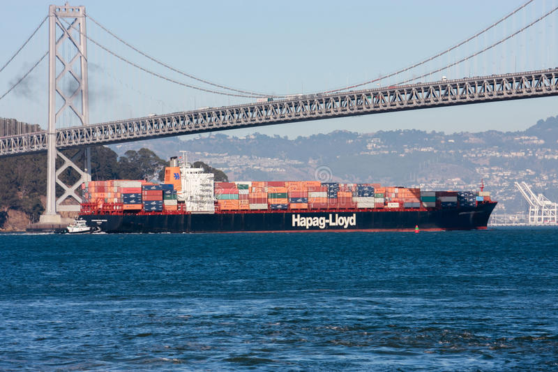 Hapag-Lloyd container ship moving under Oakland Bay Bridge royalty free stock photos