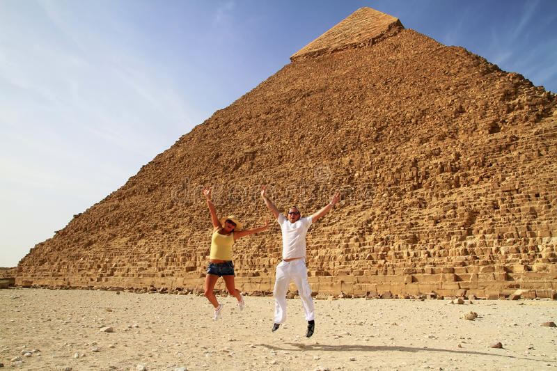 Hapiness at pyramids in Egypt. Jumping couple in Egypt at pyramids stock photography