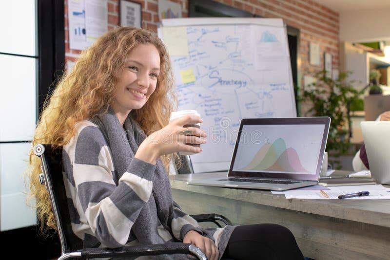 Happ caucasiansitting y sonriente de la empresaria joven hermosa imagen de archivo