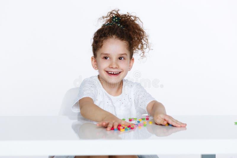 Happeness liten flicka i iklädd vit med ordnat hår, över vit bakgrund royaltyfri bild