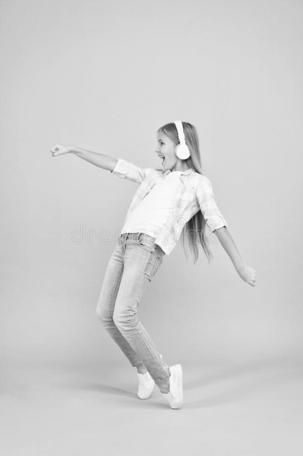 The happiest song she knows. Happy small girl dancing to music. Small girl listening to music in headphones. Cute child. Enjoying happy dance music. Dancing royalty free stock photo