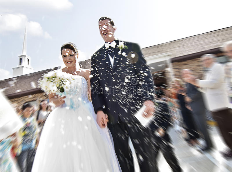 Happily Just Married. An action blur of happy bride and groom walking out of church after wedding with confetti being thrown