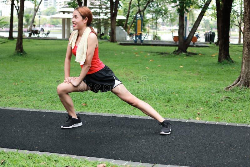 Happines Aziatische vrouw die haar benen uitrekken vóór looppas in park Geschiktheid en oefeningsconcept royalty-vrije stock foto