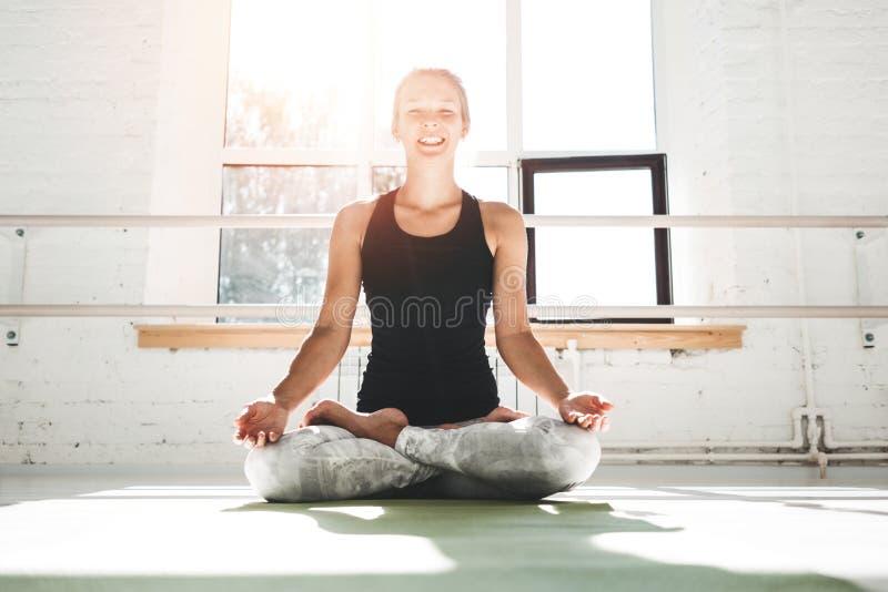 Happines passade kvinnan som praktiserande yoga poserar i idrottshall i mowrningen Kvinnlign i yoga poserar på matt kondition royaltyfri foto