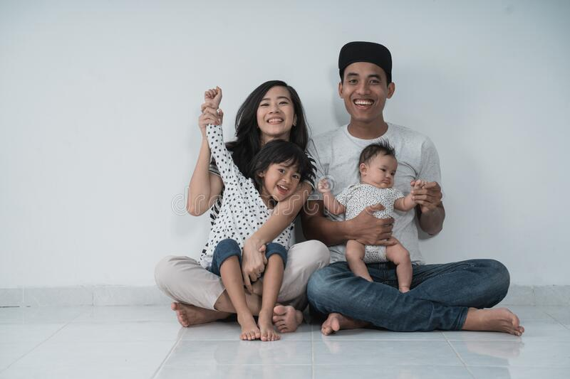 Happiness asian family with two daughter sitting on the floor have fun stock image