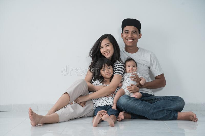 Happiness asian family with two daughter sitting on the floor have fun royalty free stock photography