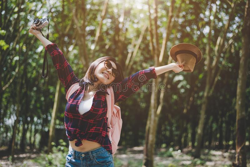 Happiness Asian traveler woman in forest with spread arms and enjoy fresh air. Relax time and Adventure concept. Vacation and stock photos