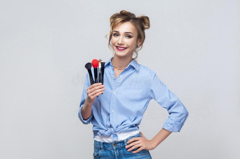 Happiness beautiful blonde girl, holding pofessional brush and l royalty free stock image