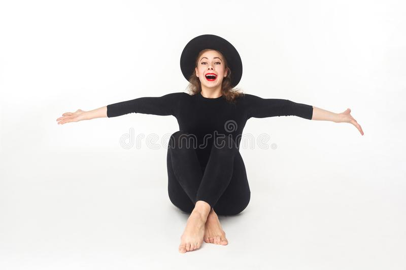 Happiness beautiful woman in hat, sitting on floor. royalty free stock images