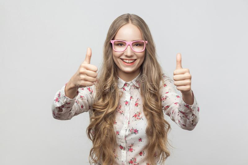 Happiness blonde girl in sunglasses, showing thumbs up, looking royalty free stock images