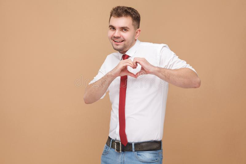 Happiness businessman showing heart shape sign. Business people concept, good and bad emotion and feelings. Studio shot, on light brown background royalty free stock image