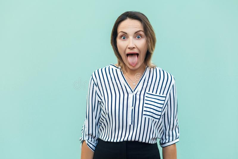 Happiness businesswoman, looking at camera with big eyes and ton. Gue out. Indoor on light blue background, studio shot royalty free stock photo