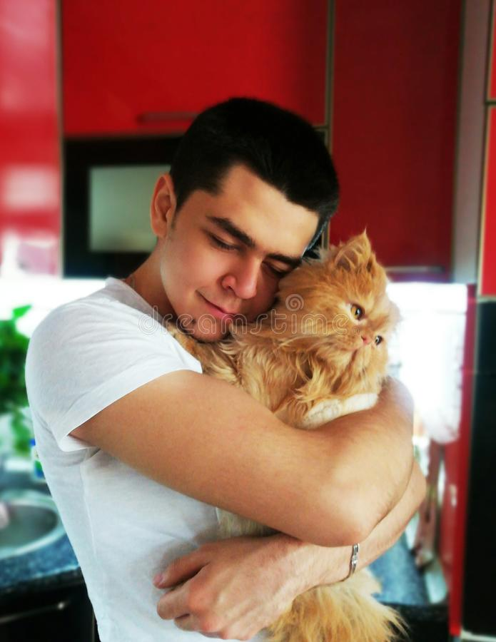 Happiness. Cat with Young Man. Orange Persian Cat. Lover Man, Hugging and Cuddling his Happy Domestic Cat Pet. Love to the animals royalty free stock photos