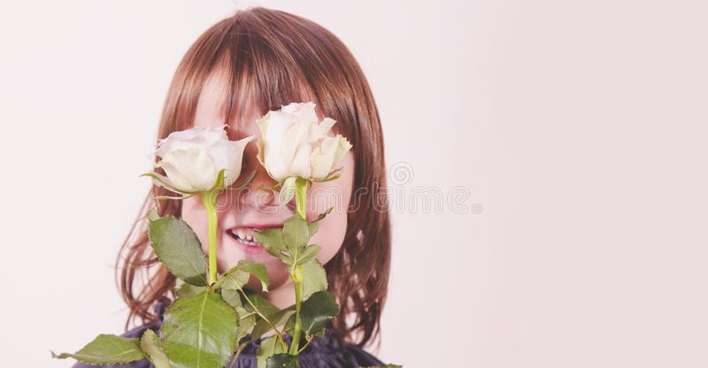 Happiness concept. Beautiful little child girl with roses flowers stock photos