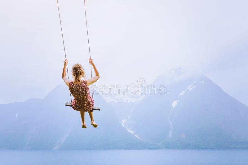 Happiness concept, happy girl child on the swing. On beautiful mountain landscape background stock photos