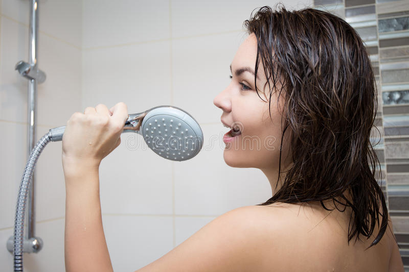 Happiness concept - portrait of young woman singing in shower royalty free stock image