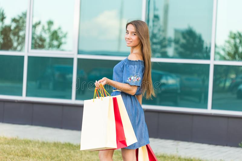 Happiness, consumerism, sale and people concept - smiling young woman with shopping bags.  stock photography