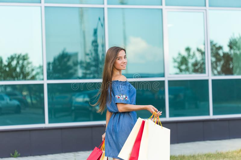 Happiness, consumerism, sale and people concept - smiling young woman with shopping bags.  royalty free stock image