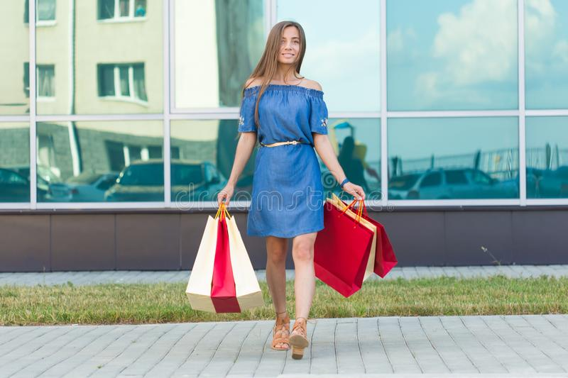Happiness, consumerism, sale and people concept - smiling young woman with shopping bags.  royalty free stock images