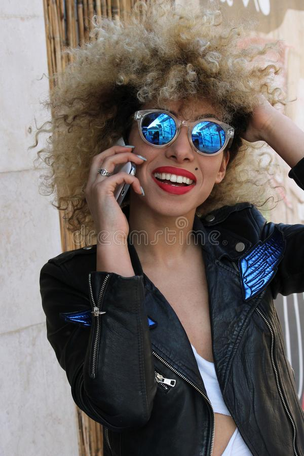 Happiness curly girl speaking at cellphone stock images