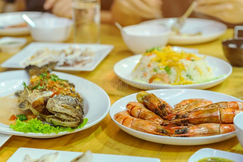 Happiness family enjoy eating with a variety of seafood dishes stock photos