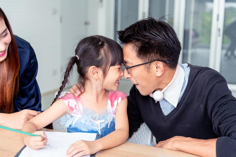 Happiness family leisure time in living room in holiday togetherness .Asian family having good time at home sitting on desk, royalty free stock image