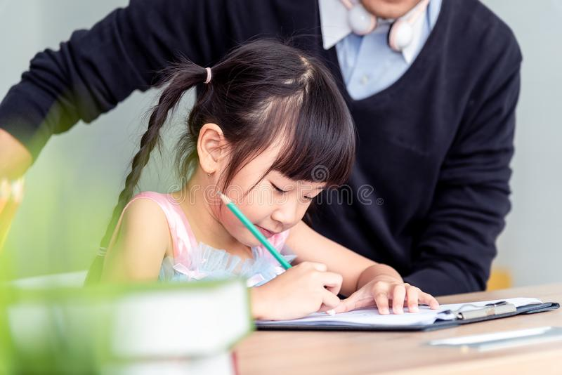 Happiness family leisure time in living room in holiday togetherness .Asian family having good time at home sitting on desk, royalty free stock photo