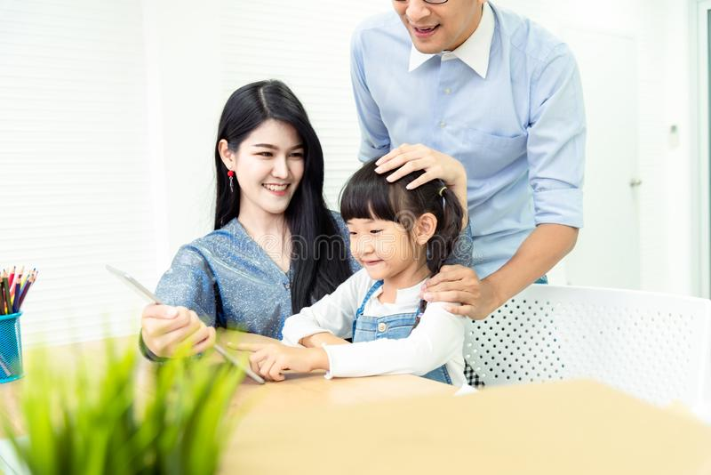 Happiness family leisure time in living room togetherness .Asian family having good time at home sitting on desk, playing ,drawing royalty free stock photography