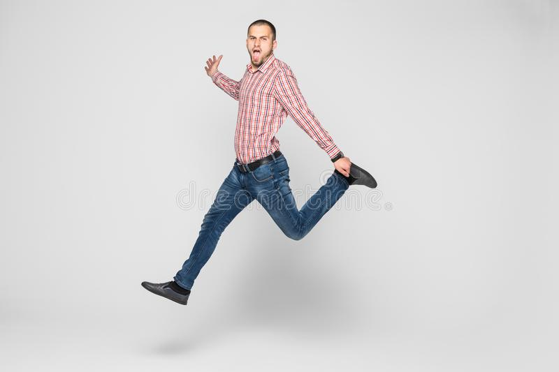 Happiness, freedom, movement and people concept - smiling young man jumping in air isolated on white royalty free stock photo