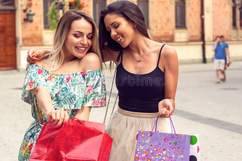 Happiness, friends, sale and fun concept - girls with shopping bags in the city royalty free stock images