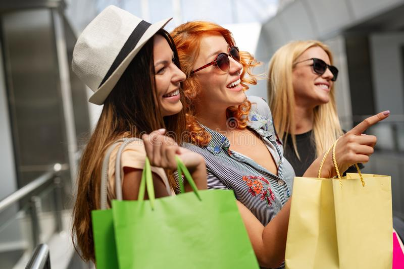 Happiness, friends, shopping and fun concept-smiling young women with shopping bags. stock image