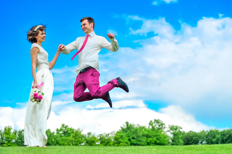 Happiness is in her hands: young and handsome bridegroom is fluttering in the air. Purpul pants royalty free stock photos