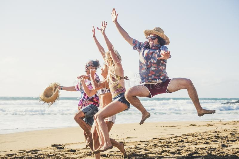 Happiness and joy for young people on vacation at the beach - enjoy outdoor leisure activity for group of friends in summer stock photography