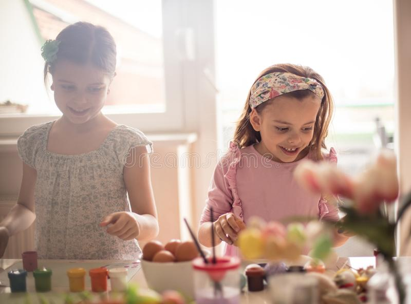 Happiness of kids do not have a price. Little girls coloring Easter egg stock images