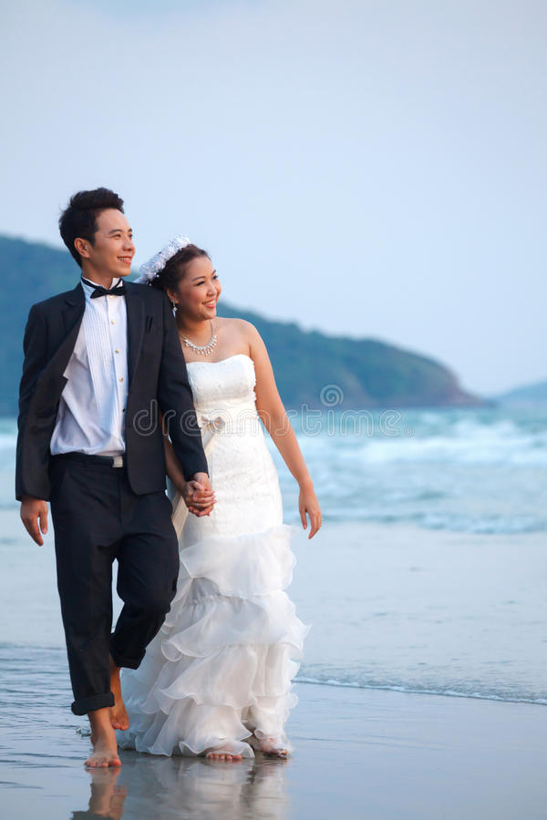 Newlywed couples Outdoor. Happiness and romantic Scene of love newlywed couples walking on the Beach stock image