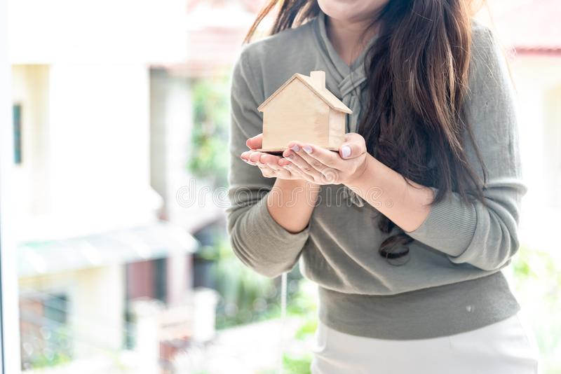 Happiness smiley woman holding small wooden mockup home model in hand. Mortgage property insurance and business real estate royalty free stock image