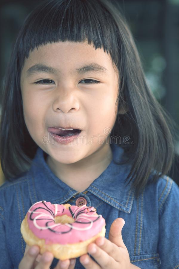 Happiness smiling face of asian children with sweet donut in han stock images