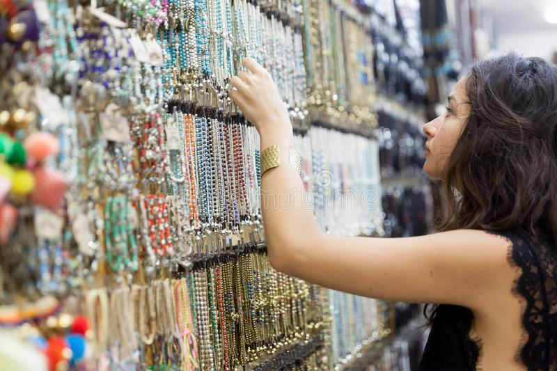Happiness souvenir shop. Cheerful young woman looking for sales in a souvenir shop stock image